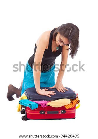 Woman sitting on luggage to close it isolated on white.