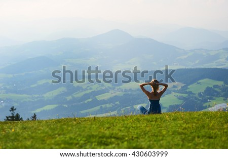 Woman sitting on mountain top. Austria