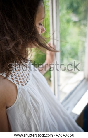 woman sitting on open window with hair fluttering in the wind (focus on hair)