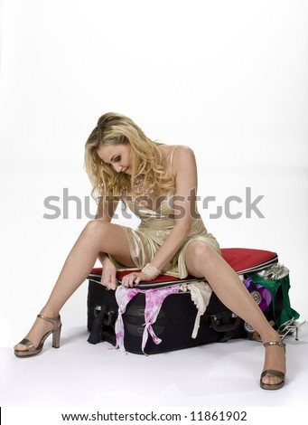 Woman sitting on overstuffed suitcase struggling with zipper, white background. - stock photo