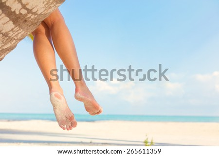 Woman sitting on palm tree at tropical beach - stock photo