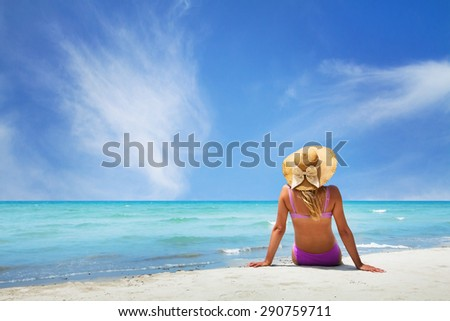 woman sitting on paradise beach - stock photo