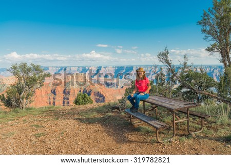 Woman sitting on Picnic Table at The Grand Caynon - stock photo