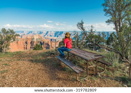 Woman Sitting on Picnic Table Looking at The Grand Caynon - stock photo