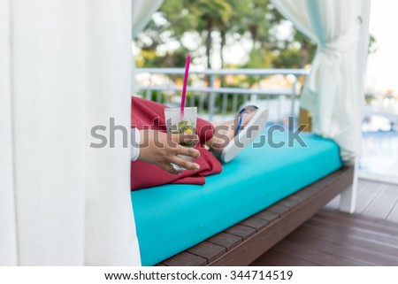 Woman sitting on resort pool and drinking juice - stock photo