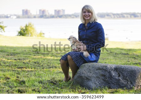 Woman sitting on rock holds little dog - stock photo