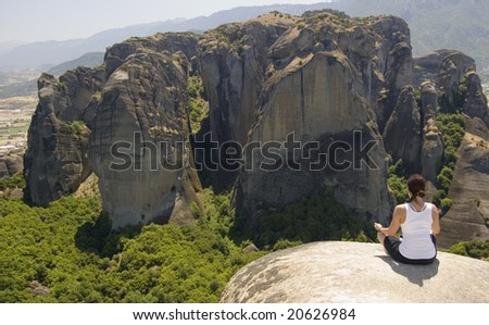 Woman sitting on rock in Meteora, Greece - stock photo