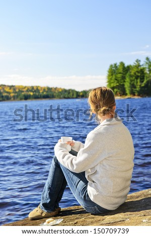 Woman sitting on rock relaxing by beautiful lake in Algonquin Park, Canada. - stock photo