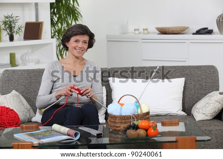 woman sitting on settee knitting - stock photo
