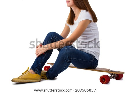 Woman sitting on skateboard isolated on a white background.