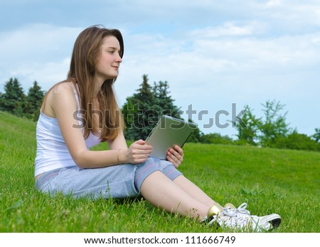 Woman sitting on sloping green grass thinking and staring into the distance with a tablet notebook in her hands