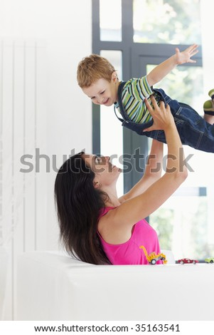 woman sitting on sofa and lifting up his son - stock photo