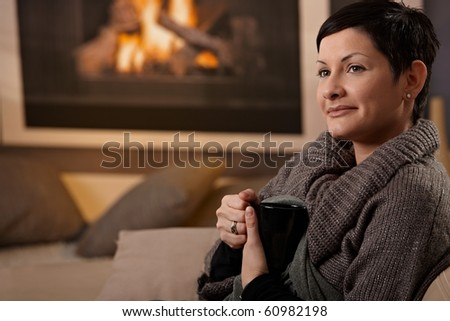 Woman sitting on sofa at home on a cold winter day, drinking hot tea, looking away. - stock photo