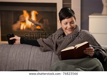 Woman sitting on sofa at home on a cold winter day, reading book.? - stock photo