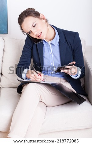 Woman sitting on sofa busy working holding two phones - stock photo