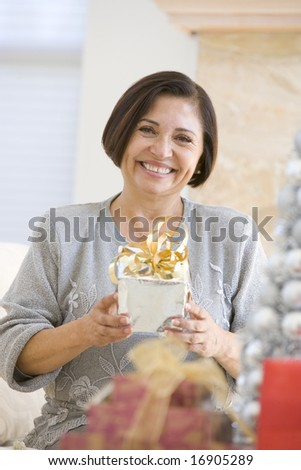 Woman Sitting On Sofa Holding A Christmas Gift - stock photo