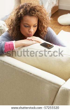 Woman Sitting On Sofa Waiting For Mobile Phone At Home - stock photo