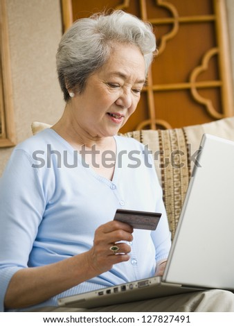 Woman sitting on sofa with laptop and credit card