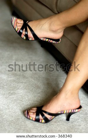 Woman sitting on sofa with legs crossed. Open colorful shoes. Shallow DOF, focus on left foot. - stock photo
