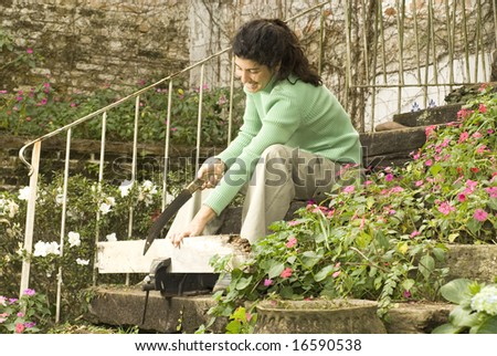 Woman sitting on stairs holds a board in a vice. She is smiling and sawing the board. Horizontally framed photo. - stock photo