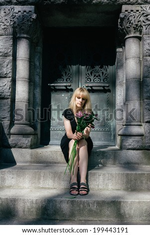 Woman sitting on steps of mausoleum with flowers in cemetery for grief, loss and death concept - stock photo