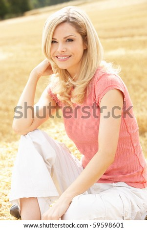 Woman Sitting On Straw Bales In Harvested Field - stock photo