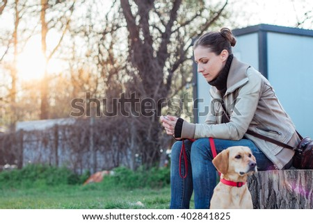 Woman sitting on stump in backyard with her dog - stock photo