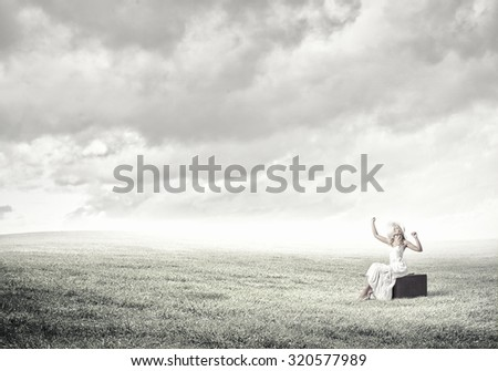 Woman sitting on suitcase in white long dress and hat