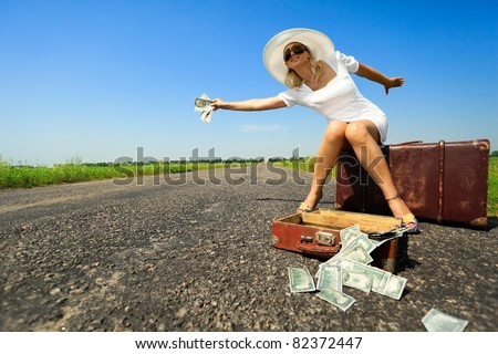 Woman  sitting on suitcase with cash stops the car on countryside road - stock photo