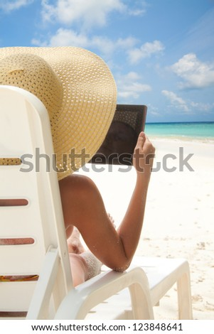 Woman sitting on the beach and browsing internet with tablet computer sitting in the deck chair - stock photo