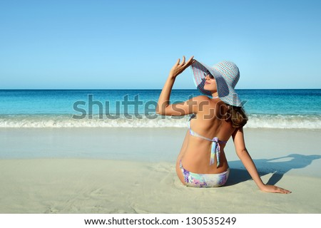 Woman sitting on the beach turned wistfully looking at the sky in the background of the Caribbean. - stock photo