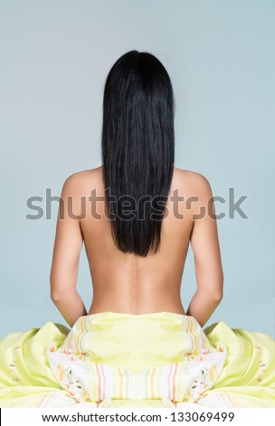 Woman sitting on the bed with back toward camera, light background - stock photo