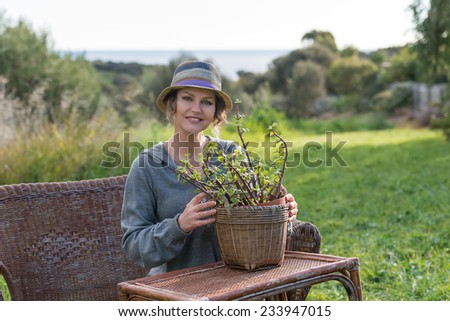 Woman sitting on the bench in nature  and holding a pot with plant