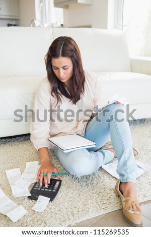 Woman sitting on the carpet checking bills in the living room - stock photo