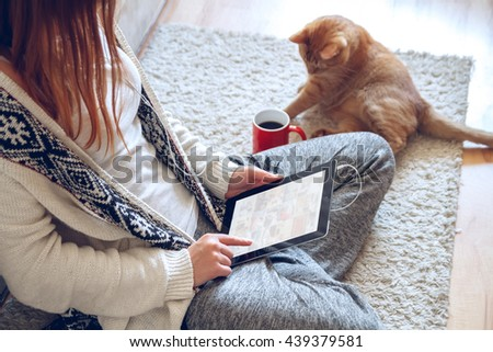 Woman sitting on the carpet near the sofa using a tablet with headphones,drinking coffee from a red cup. Next to it lies a thick red cat.  Online education concept. e-learning. . Pet shop concept - stock photo