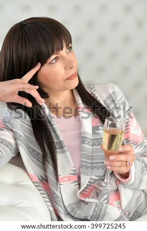woman sitting on the couch with a glass - stock photo