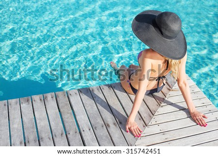 Woman sitting on the deck by the pool - stock photo