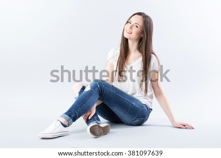 Woman sitting on the floor and smiling. - stock photo