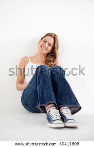 Woman sitting on the floor - isolate over a white background - stock photo