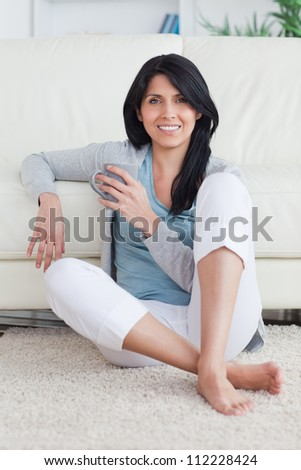 Woman sitting on the floor while holding a mug in a living room