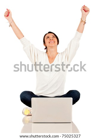 Woman sitting on the floor with a laptop computer and arms up - isolated - stock photo