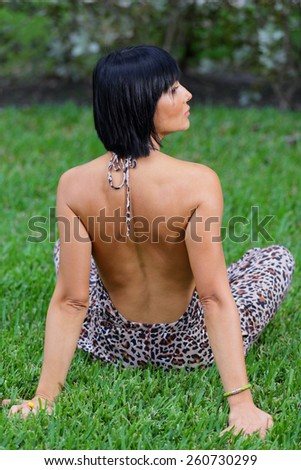 Woman sitting on the grass with an open back dress - stock photo