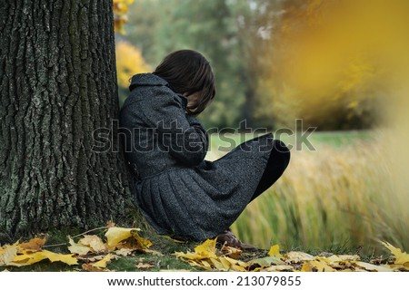 Woman sitting on the ground and crying in the park - stock photo