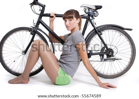 woman sitting on the ground with a bike