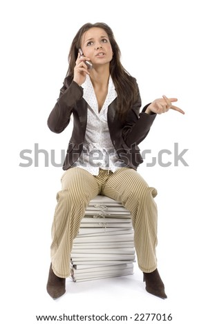 woman sitting on the heap of files, talking mobile phone (white background) - stock photo