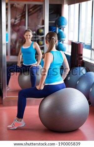 Woman sitting on the pilates ball in front of mirror in the gym - stock photo