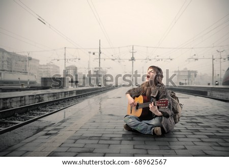 Woman sitting on the platform of a train station and singing and playing guitar - stock photo
