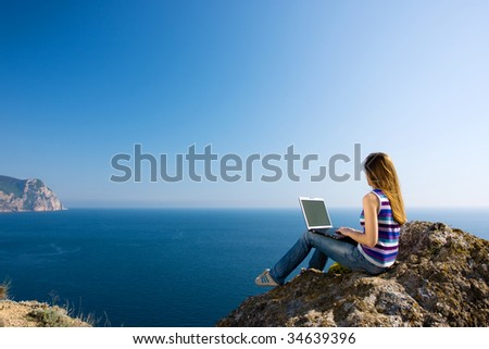 woman sitting on the rock with laptop near the sea - stock photo