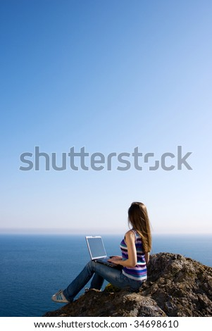 woman sitting on the rock with laptop near the sea