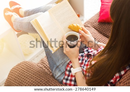 Woman sitting on the sofa reading a book holding her coffee mug in living room at home - stock photo